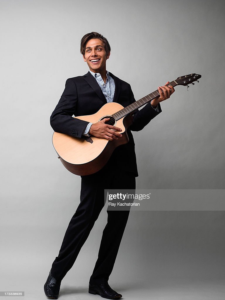 Man smiling and playing guitar