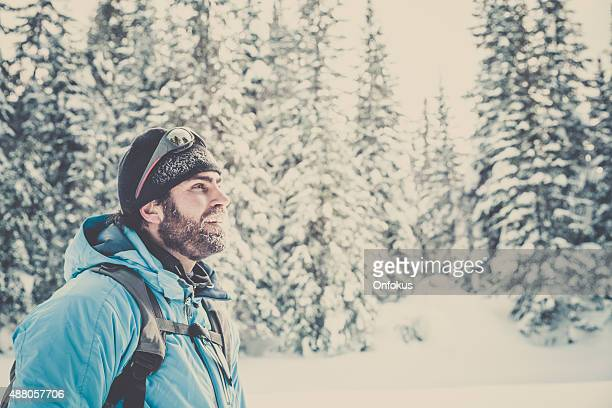 Man Smiling and Resting in a snow covered forest