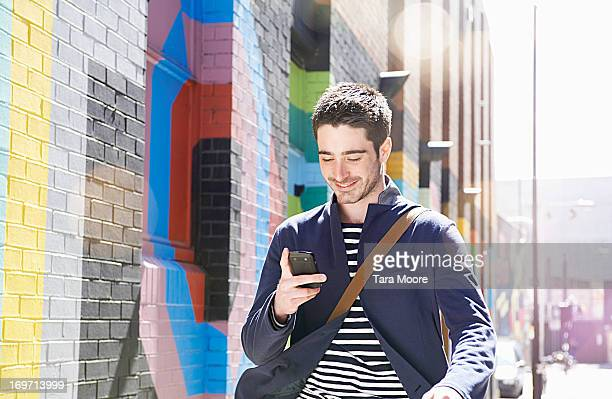 man smiling and walking in city with mobile