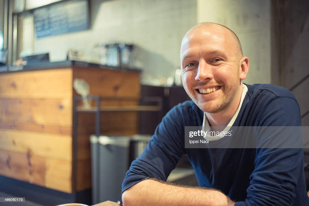 Man smiling at camera in cafe