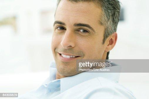 Man smiling at camera, looking over shoulder, portrait