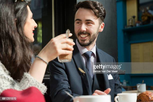 Man smiling at partner, drinking coffee in urban cafe.