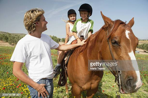 Man smiling at son and daughter (9-11) on horse