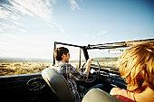 Man smiling driving convertible on rural road