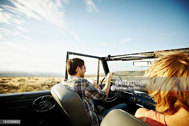 Man smiling driving convertible on rural road