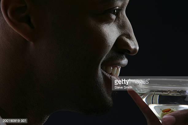 Man smiling, holding martini, profile