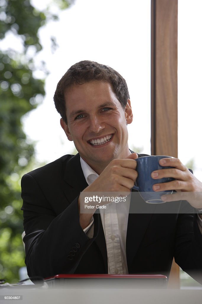 man smiling holding mug : Stock Photo