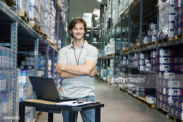 man smiling in factory aisle