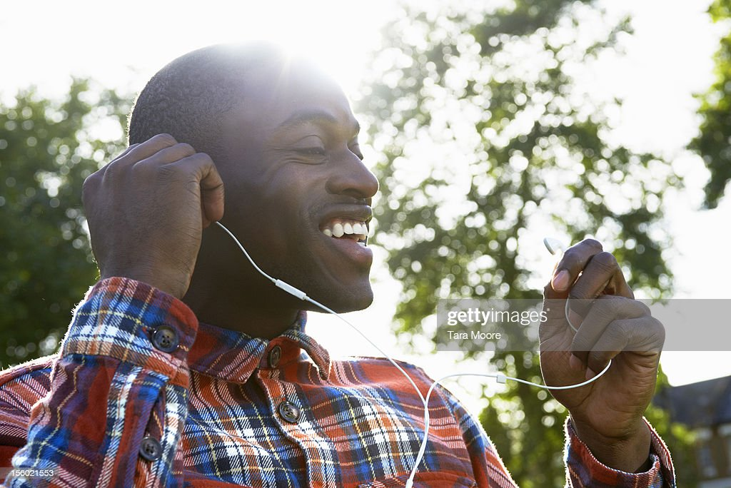 man smiling in park putting in ear phones : Stock Photo