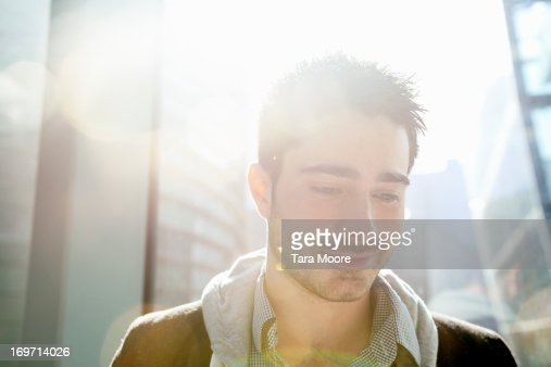 man smiling in sunlight flare in office