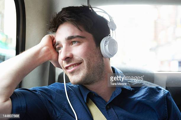 man smiling in taxi with headphones