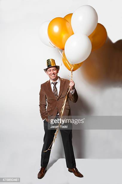 man smiling on white holding balloons on new years