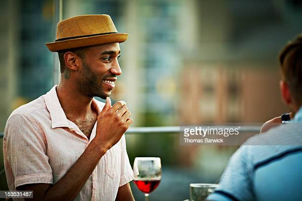 Man smiling sitting at table on rooftop deck