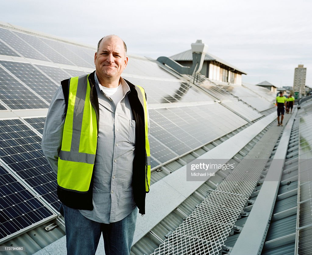 Man smiling to camera on solar panelled roof : Stock Photo