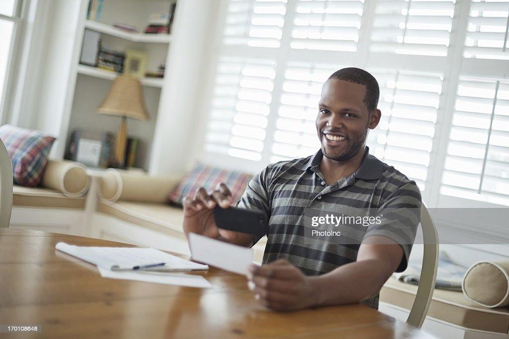 Man Smiling While Depositing Check Through Smart Phone