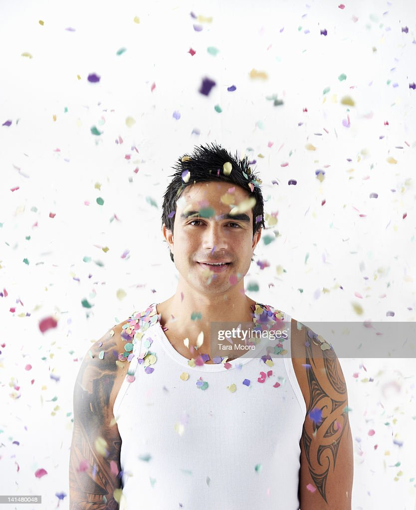 man smiling with confetti falling on head : Stock Photo