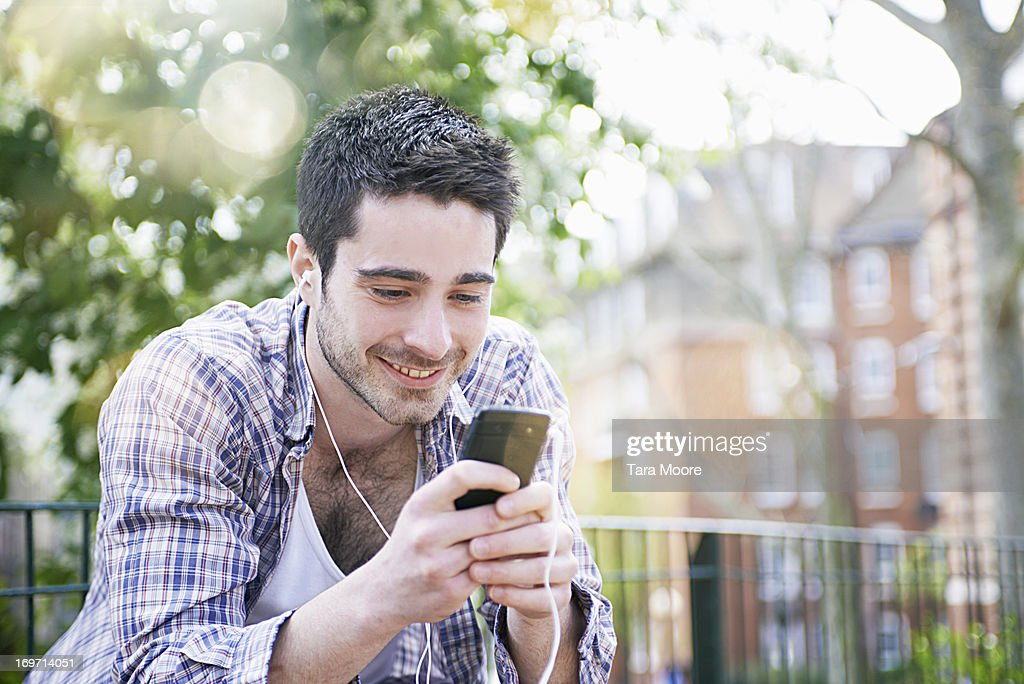 man smiling with earphones and mobile : Stock Photo