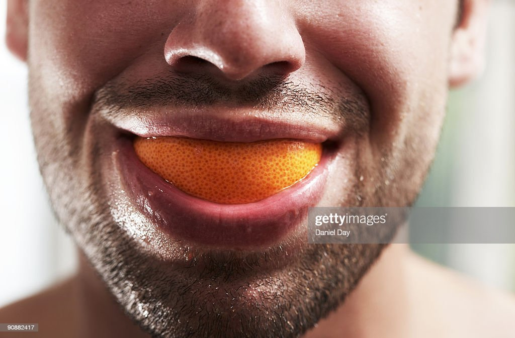 Man smiling with fruit in mouth : Stock Photo