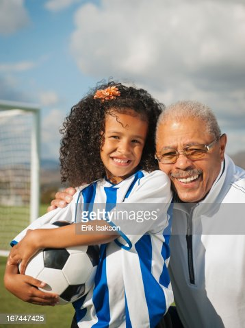 Man smiling with granddaughter on soccer field : Stock Photo