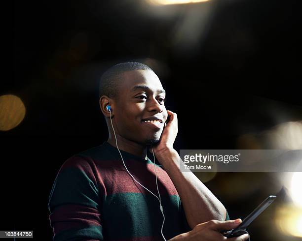 man smiling with headphones and mobile phone