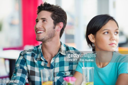 Man smiling with his girlfriend looking sad in a restaurant : Stock Photo