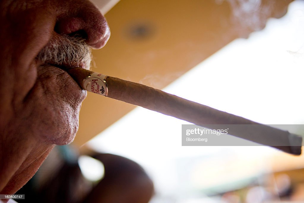A man smokes a cigar in front of a shop on Calle 8, or Eighth Street, in the Little Havana district of Miami, Florida, U.S., on Wednesday, Feb. 20, 2013. U.S. exports in the travel and tourism sector reached $168.1 billion in 2012, up 10.1 percent from the year-ago level of $152.7 billion, according to data released Feb. 22 by the Commerce Department's International Trade Administration. Photographer: Ty Wright/Bloomberg via Getty Images