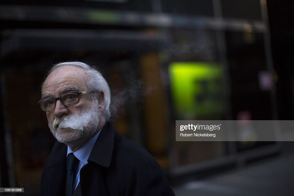 A man smokes a cigar on a sidewalk January 7, 2013 in the Manhattan borough of New York.