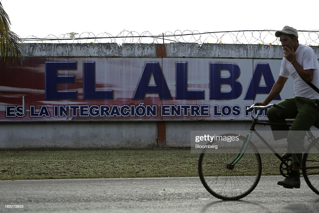 A man smokes a cigarette as he rides a bicycle past a billboard for ALBA, a regional trading bloc founded by Venezuela and Cuba, in Havana, Cuba, on Wednesday, March 6, 2013. Cuba's government praised Venezuelan President Hugo Chavez following his death yesterday for uniting the people of Latin America and pledged loyalty to the continuation of his Bolivarian Revolution, according to the statement in the state-run Granma website. Photographer: Noah Friedman-Rudovsky/Bloomberg via Getty Images