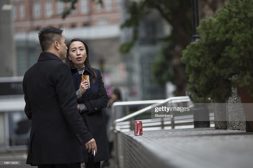 A man smokes a cigarette as he talks with a woman in Hong Kong, China, on Friday, Jan. 4, 2013. Chief Executive Leung Chun-ying, who has been buffeted by student protests and low popularity since taking office on July 1, has pledged to tackle Asia's biggest wealth gap as the division between poor and rich widened to its worst level since at least 1971. Photographer: Jerome Favre/Bloomberg via Getty Images