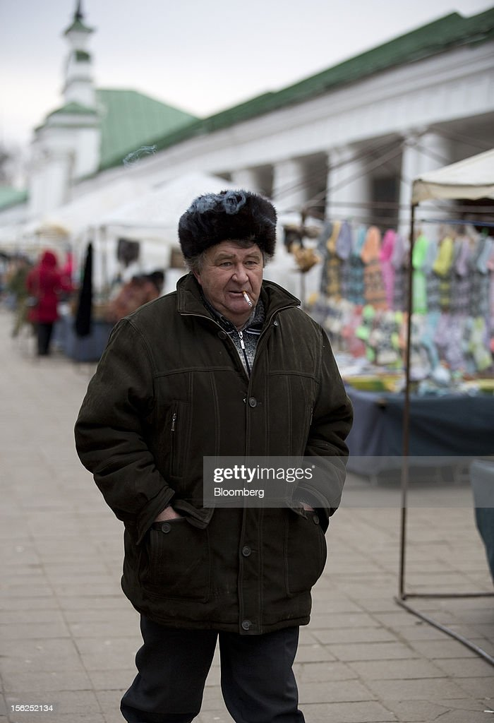 A man smokes a cigarette as he walks past street stalls in Suzdal, Russia, on Sunday, Nov. 11, 2012. Russia has one of the world's lowest retirement ages, set in 1932 during the Stalin era. Photographer: Andrey Rudakov/Bloomberg via Getty Images