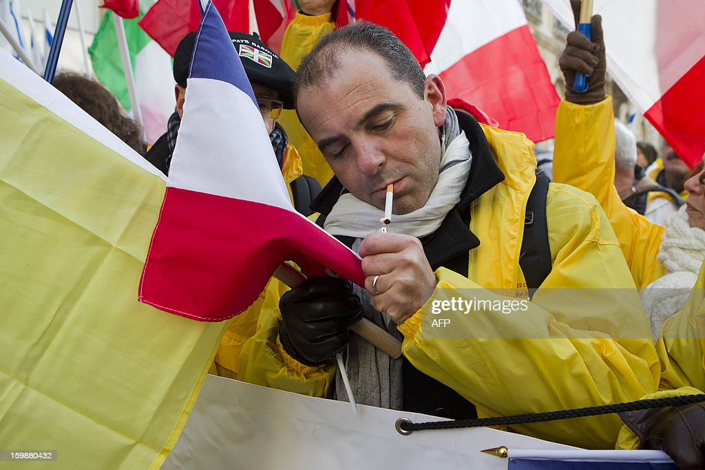 A man smokes a cigarette during a demonstration of CEDT (Confederation Europeene des Detaillants en Tabac) the European Confederation of Tobacco Retailers, against the propoition for new guidelines on the packaging of tobacco products, on January 22, 2013 in Brussels.