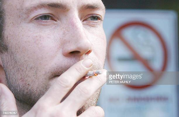 A man smokes a cigarette in Belfast northern Ireland 30 April 2007 as smokers can no longer light up in bars or other public places across Northern...