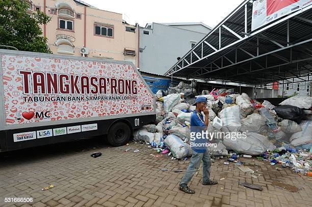 A man smokes a cigarette in front of a truck parked outside the Mutiara Trash Bank in Makassar South Sulawesi Province Indonesia on Friday March 11...