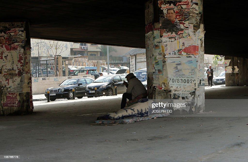 A man smokes a cigarette next to a sleeping homeless man under a bridge in Beirut on December 28, 2012. AFP PHOTO / JOSEPH EID