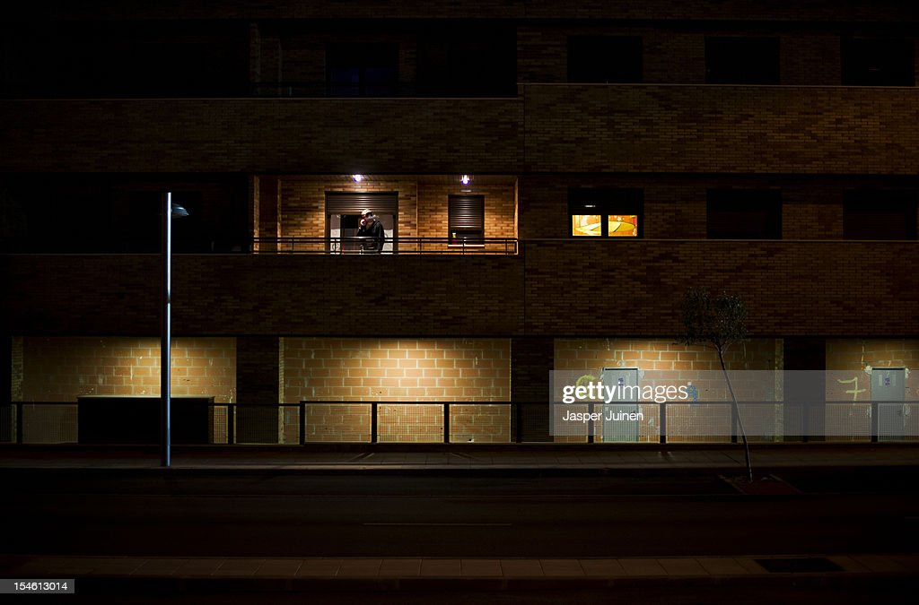 A man smokes a cigarette on his balcony in between apartment buildings with the exterior window shutters closed, and where below shops should have arisen, on October 22, 2012 in Sesena, Spain. With a housing backlog of more than 1.2 million unsold newly build homes, banks in Spain have recenlty started to sell their real estate assets with discounts, some upto 80 percent, slashing prices to a level not seen for over 20 years. With morgages of 100 percent, some experts worry that mistakes from the past are repeated again.
