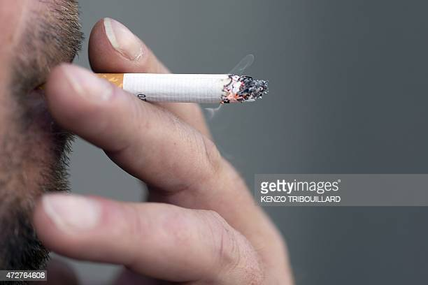 A man smokes a cigarette on May 9 2015 in Paris AFP PHOTO / KENZO TRIBOUILLARD