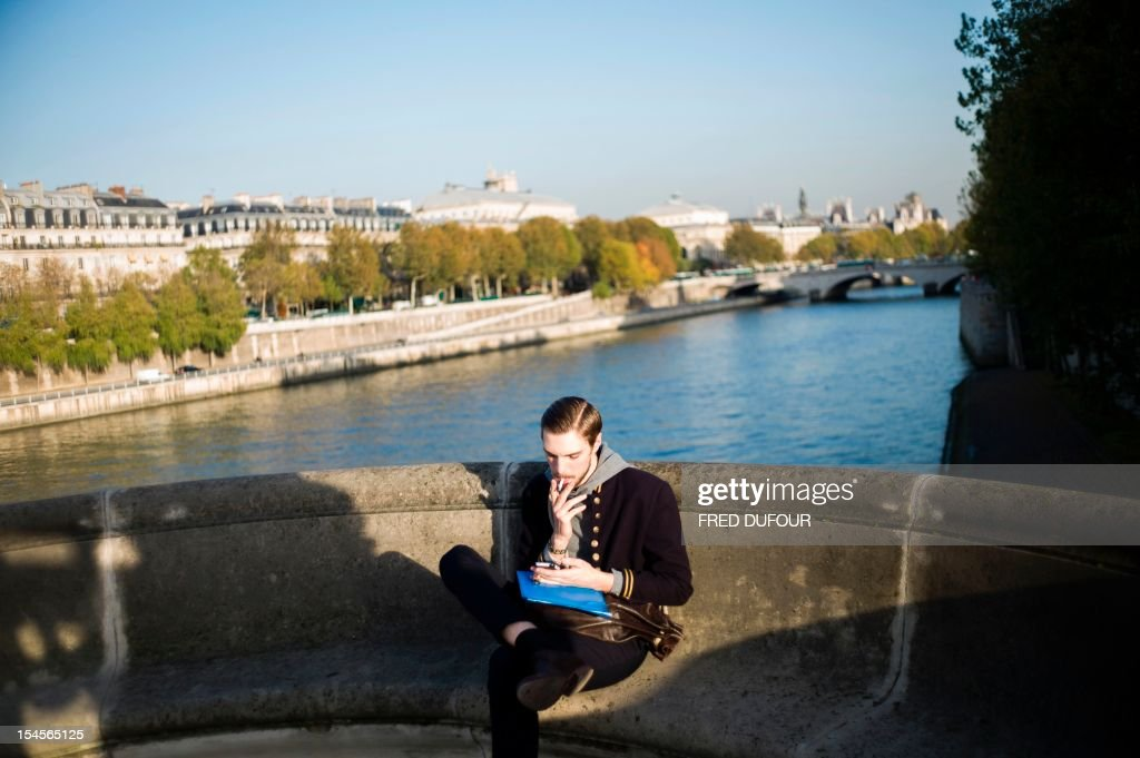 A man smokes a cigarette on the Pont Neuf, a famous bridge of Paris on October 22, 2012.
