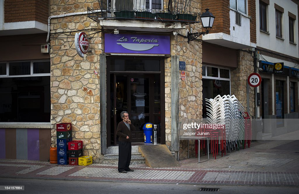A man smokes a cigarette oustside a bar on October 12, 2012 in the small industrial town of Villacanas, Spain. During the boom years, where in its peak Spain built some 800,000 houses a year, more than Britain, Germany and France combined, and millions of wooden doors where needed, the people of Villacanas were part of a proud elite enjoying high wages and permanent jobs. Almost all of those doors used came from this small industrial town in the La Mancha province, some seven million a year, leaving with truck loads at the same time, from the now empty and silent Villacanas industrial park. With Spain in recession and the housing bubble busted, the door industry is shattered and unemployment in Villacanas, zero for nearly a generation, is rising fast.
