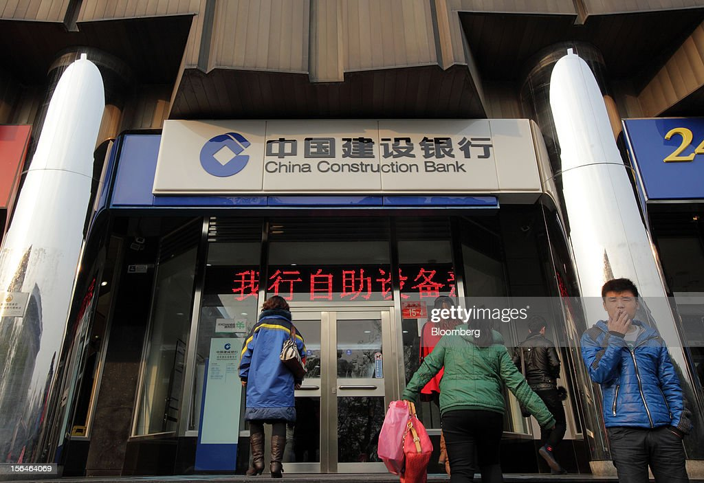 A man smokes a cigarette outside a China Construction Bank Corp. branch in Beijing, China, on Thursday, Nov. 15, 2012. China Construction Bank is the nation's second-largest lender by assets. Photographer: Tomohiro Ohsumi/Bloomberg via Getty Images