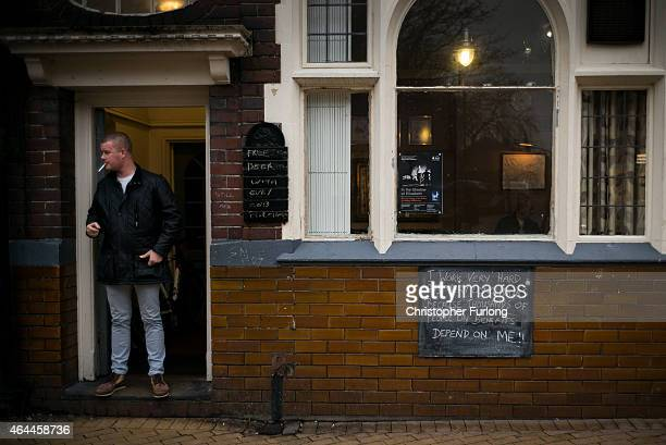 A man smokes a cigarette outside a pub in Bilston West Midlands on February 11 2015 in Bilston United Kingdom As the United Kingdom prepares to vote...