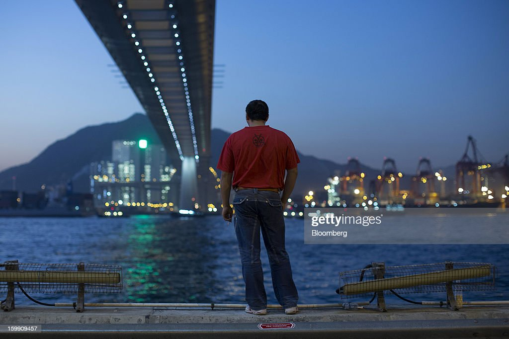 A man smokes a cigarette while standing opposite the Kwai Tsing Container Terminals with Stonecutters Bridge overhead in Hong Kong, China, on Monday, Jan. 21, 2013. Hong Kong is scheduled to release export figures for December on Jan. 24. Photographer: Jerome Favre/Bloomberg via Getty Images