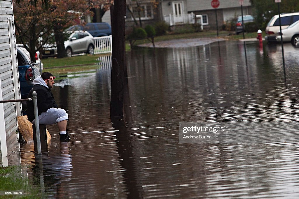 A man smokes a cigarette while watching flood waters caused by Hurricane Sandy from his driveway on October 30, 2012 in New York City. The storm has claimed at least 40 lives in the United States, and has caused massive flooding across much of the Atlantic seaboard. US President Barack Obama has declared the situation a 'major disaster' for large areas of the US East Coast including New York City.