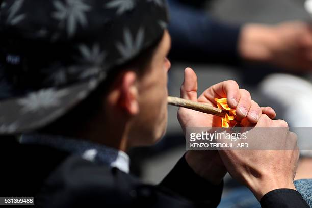 A man smokes a 'joint' during a demonstration to call for the legalisation of marijuana on May 14 2016 in Paris France / AFP / KENZO TRIBOUILLARD