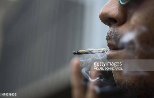 A man smokes a joint during a march calling for the legalization of marijuana at Paulista Avenue in Sao Paulo Brazil on May 23 2015 Members of the...