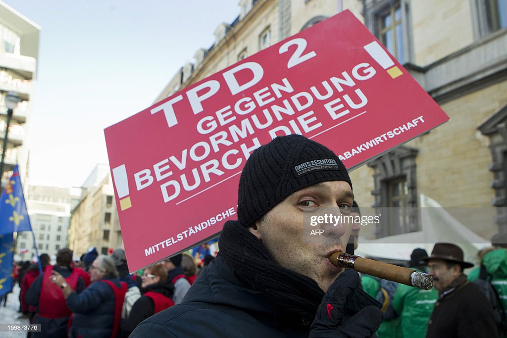 A man smokes a large cigar during a demonstration called by the CEDT (Confederation Europeenne des Detaillants en Tabac, the European Confederation of Tobacco Retailers) against the propoition for new guidelines on the packaging of tobacco products on January 22, 2013 in Brussels. AFP PHOTO / BELGA - KRISTOF VAN ACCOM