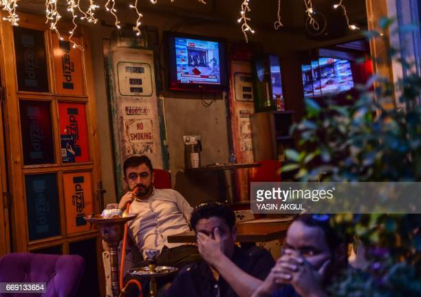 A man smokes a shisha as others follow the referendum results on television near Taksim square in Istanbul on April 16 2017 The 'Yes' campaign to...