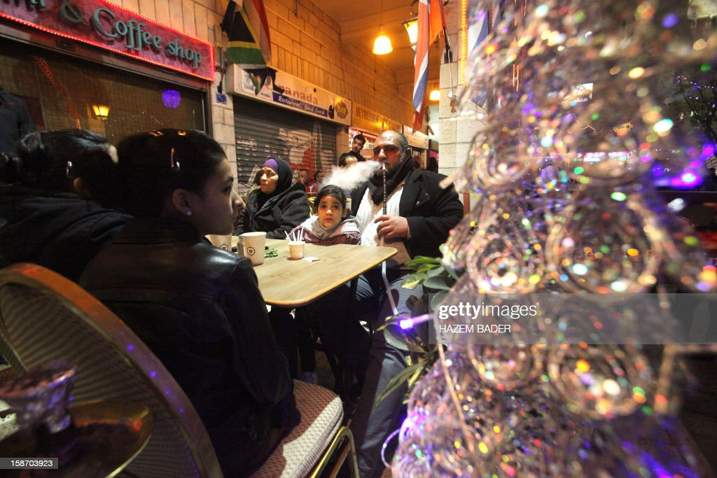 A man smokes a water pipe at a coffee shop close to the Church of the Nativity as people gather for Christmas eve celebrations in the biblical West Bank city of Bethlehem, believed to be the birthplace of Jesus Christ, on December 24, 2012. Thousands of Palestinians and tourists were flocking to Bethlehem to mark Christmas.