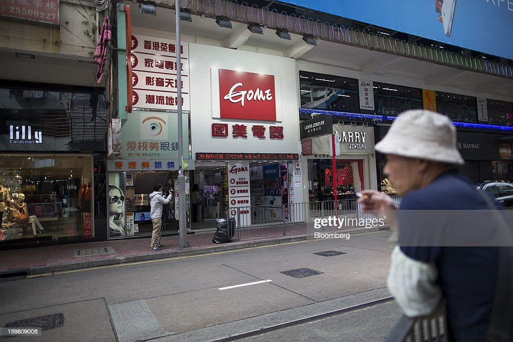 A man smokes across from the entrance of a Gome-branded store in the shopping district of Causeway Bay in Hong Kong, China, on Monday, Jan. 21, 2012. Gome Electrical Appliances Holding Ltd.'s stocks tumbled in Hong Kong after the company confirmed a report it is closing Gome-branded stores in the city. Photographer: Jerome Favre/Bloomberg via Getty Images