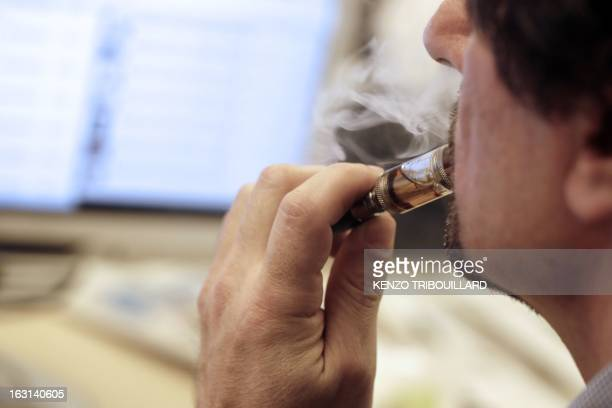 A man smokes an electronic cigarette in his office on March 05 2013 in Paris AFP PHOTO / KENZO TRIBOUILLARD