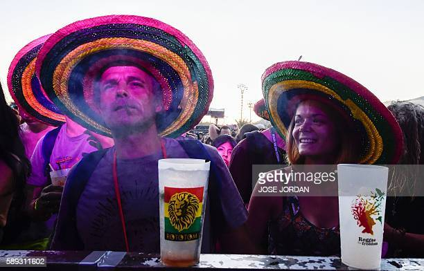 A man smokes as a woman looks on during the Rototom Sunsplash European Reggae Festival in Benicassim Castellon province on August 13 2016 The Rototom...
